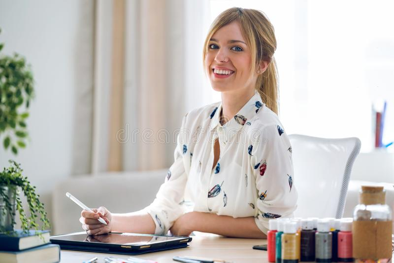 Glimlachende mooie jonge ontwerpervrouw die met haar digitale tablet werken terwijl het bekijken de camera op het kantoor royalty-vrije stock foto's