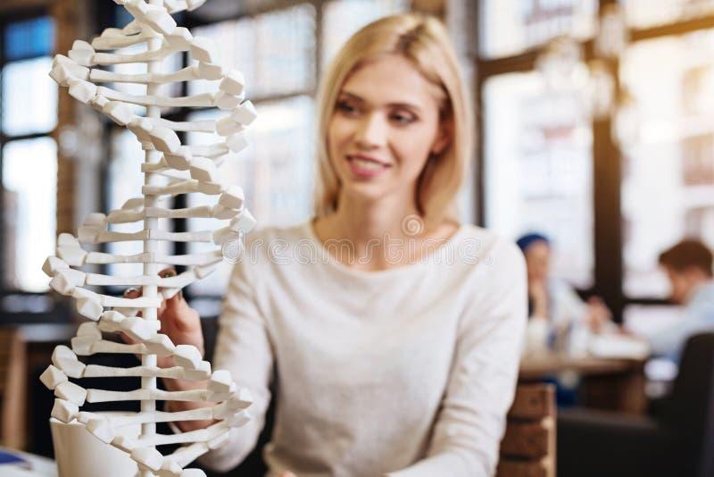 Glimlachende mooie jonge student die DNA-model bestuderen stock foto's