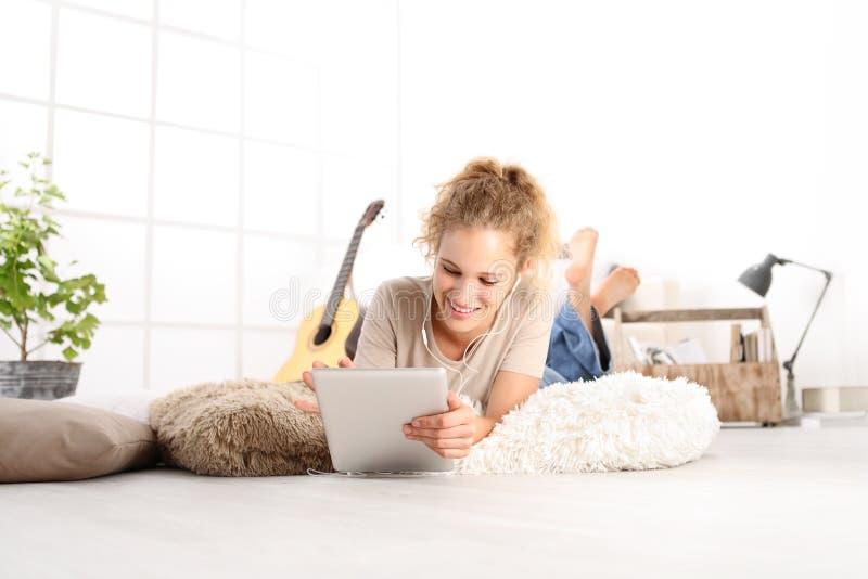 Glimlachende Mooie jonge vrouw die een digitale tablet met earpho gebruiken royalty-vrije stock foto's