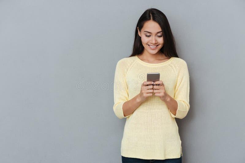 Glimlachende mooie jonge vrouw die en celtelefoon bevinden zich met behulp van royalty-vrije stock afbeelding