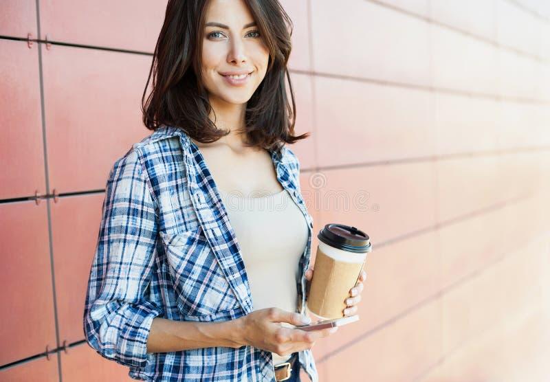Glimlachende mooie jonge vrouw die smartphone in de stad met behulp van royalty-vrije stock foto's