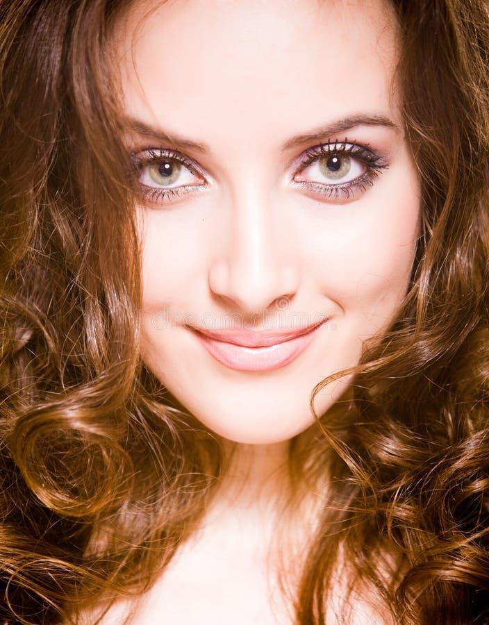 Glimlachende mooie jonge vrouw met lange krul royalty-vrije stock afbeelding