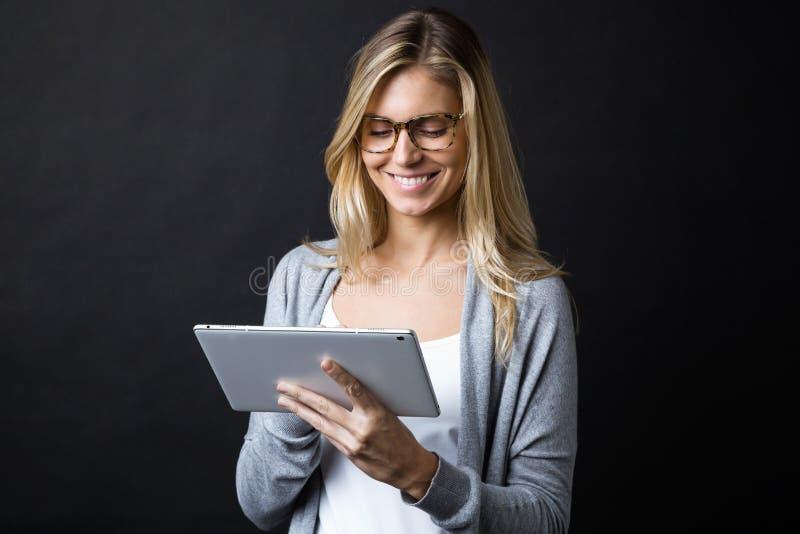 Glimlachende mooie jonge vrouw met oogglazen die met digitale tablet over zwarte achtergrond werken stock foto
