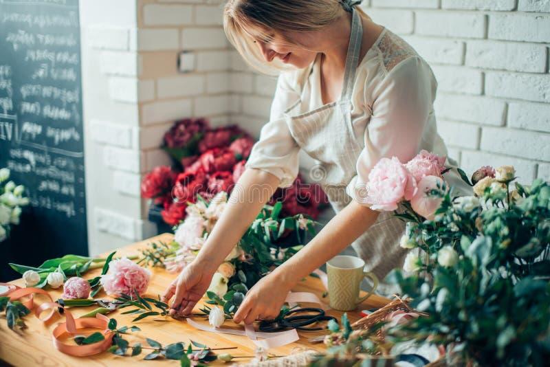 Glimlachende mooie jonge vrouwenbloemist die installaties in bloemwinkel schikken royalty-vrije stock foto's