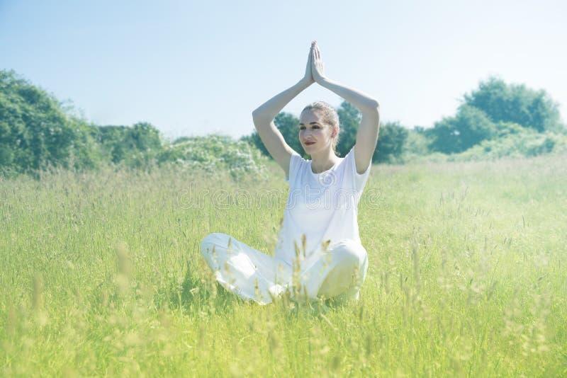 Glimlachende mooie jonge yogavrouw die voor gestemde geestelijke mindfulness bidden royalty-vrije stock afbeelding