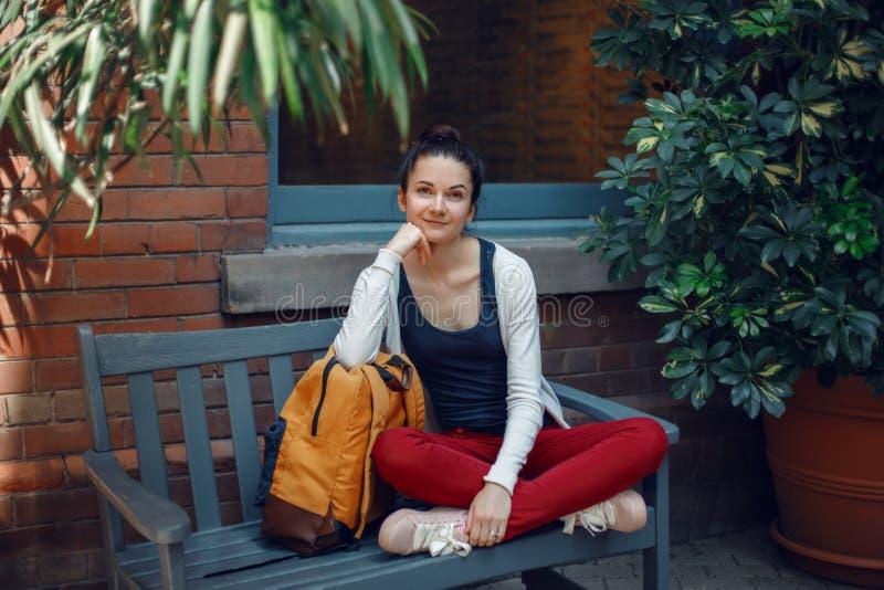 Glimlachende mooie Kaukasische jonge meisjesvrouw in witte sweater en rode jeans, die met de gele rugzak van de reiszak op bank z stock foto
