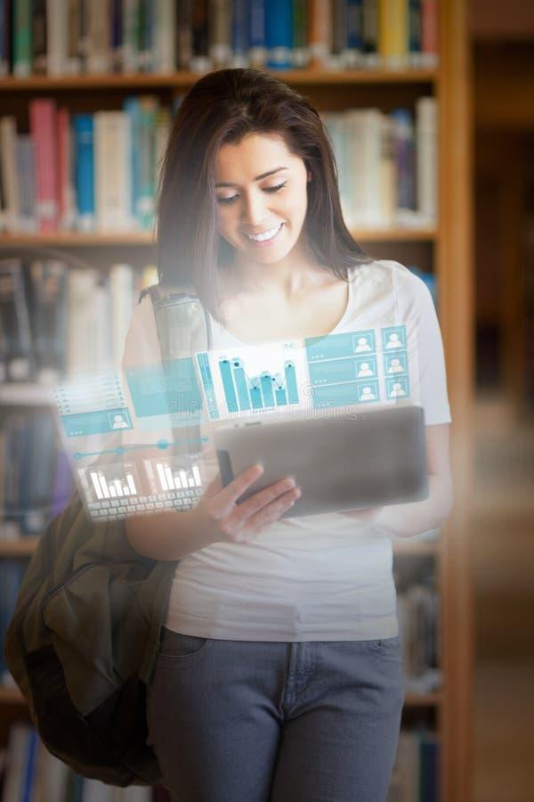 Glimlachende mooie student die aan haar futuristische tablet werken stock afbeeldingen
