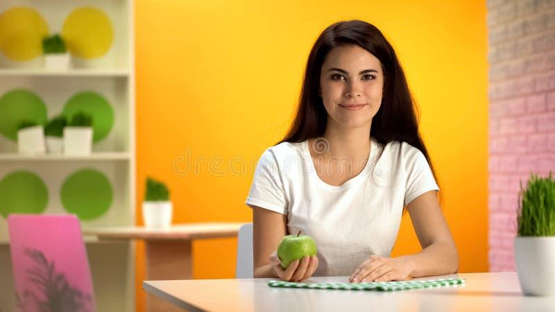 Glimlachende mooie vrouw die groene appel in hand houden, gezondheidszorg, vegetarisch dieet stock foto's