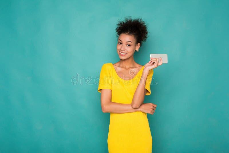 Glimlachende mooie vrouw die mobiele telefoon houden stock afbeeldingen