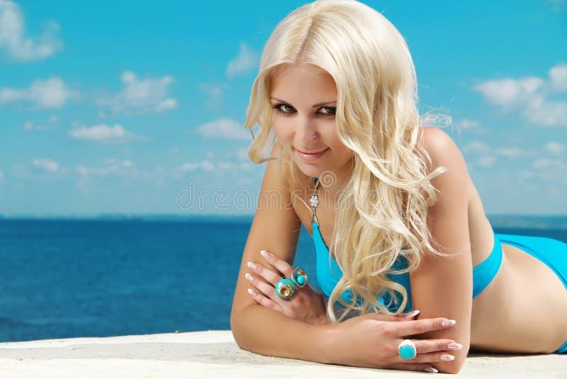 Glimlachende mooie vrouw die op strandoverzees zonnebaadt royalty-vrije stock foto's