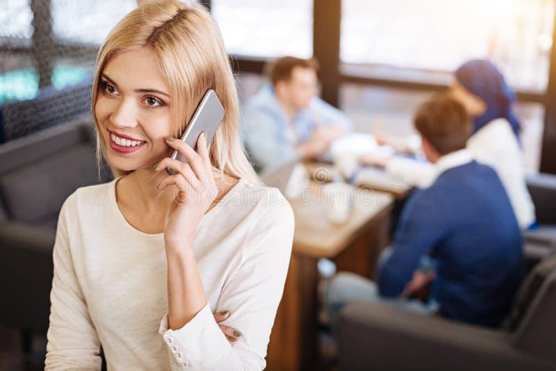 Glimlachende mooie vrouw die op telefoon in de koffie spreken stock foto