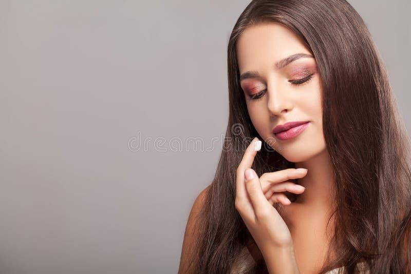 Glimlachende mooie vrouw die room op haar gezicht toepassen stock afbeeldingen