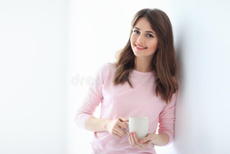 Glimlachende mooie vrouw met kop van koffie op witte achtergrond royalty-vrije stock fotografie