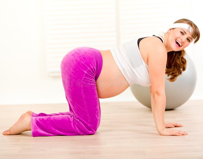Glimlachende mooie zwangere vrouw die gymnastiek maakt stock foto