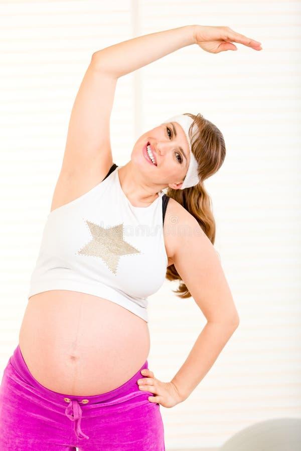 Glimlachende mooie zwangere vrouw die gymnastiek maakt stock afbeelding