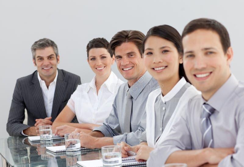 Glimlachende multi-etnische bedrijfsmensen in een vergadering stock afbeelding