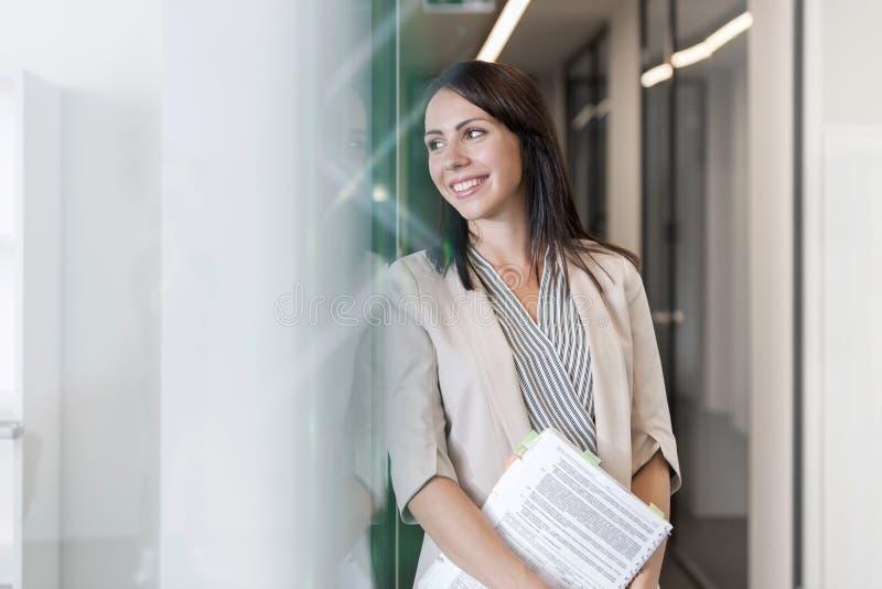 Glimlachende nadenkende onderneemster met documenten op kantoor stock foto's