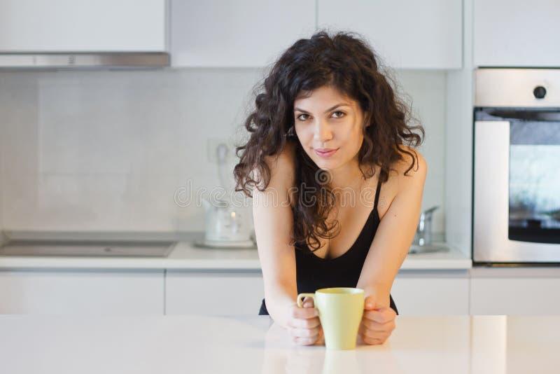 Glimlachende natuurlijke vrouw in keuken stock afbeeldingen
