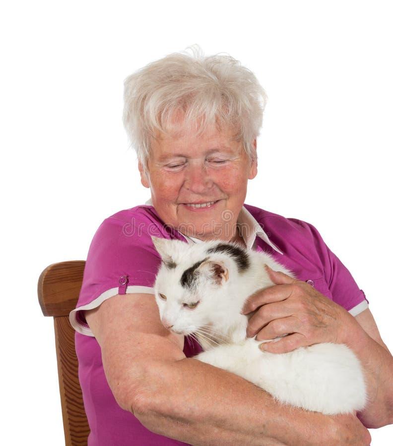 Glimlachende oma die haar kat houdt stock foto