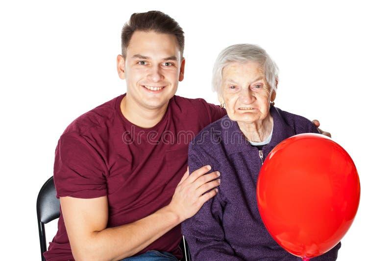 Glimlachende oma en kleinzoon met rode ballon royalty-vrije stock afbeeldingen