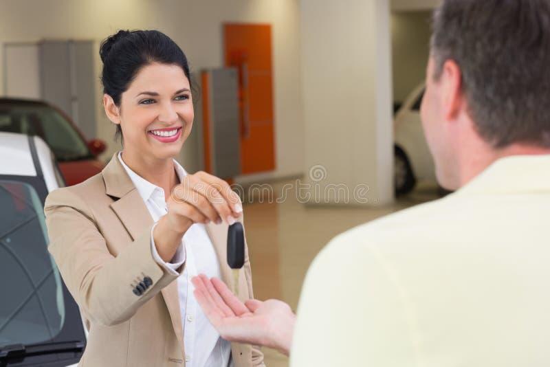 Glimlachende onderneemster die autosleutel geven aan gelukkige klant stock foto