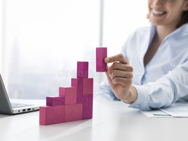 Glimlachende onderneemster die een succesvolle financi?le grafiek bouwen royalty-vrije stock afbeeldingen