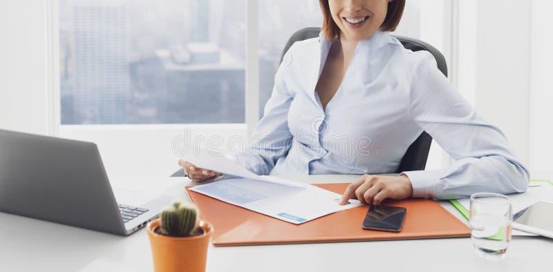 Glimlachende onderneemster die in het bureau en het controleren van grafieken werken royalty-vrije stock afbeeldingen