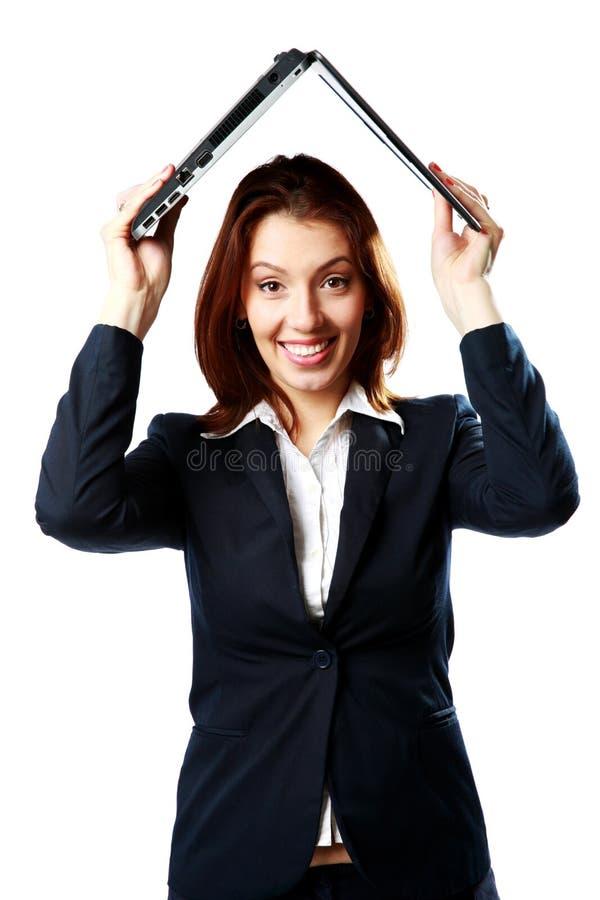 Glimlachende onderneemster die laptop boven haar hoofd zoals een dak houden royalty-vrije stock foto's