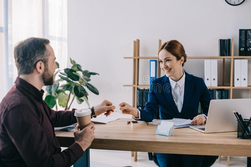 glimlachende onderneemster die lege kaart geven aan cliënt met koffie om op het werk te gaan stock afbeeldingen