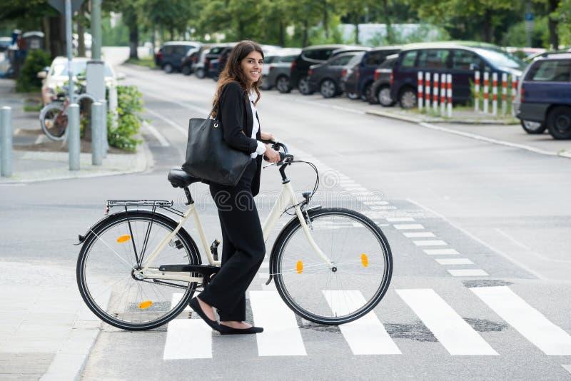 Glimlachende Onderneemster With Handbag Commuting op Fiets stock fotografie