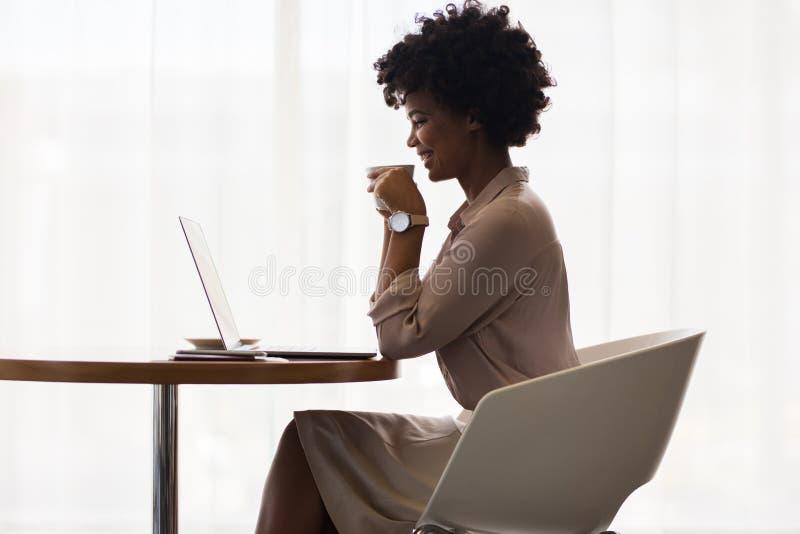 Glimlachende onderneemster het drinken koffie en het gebruiken van laptop stock afbeelding