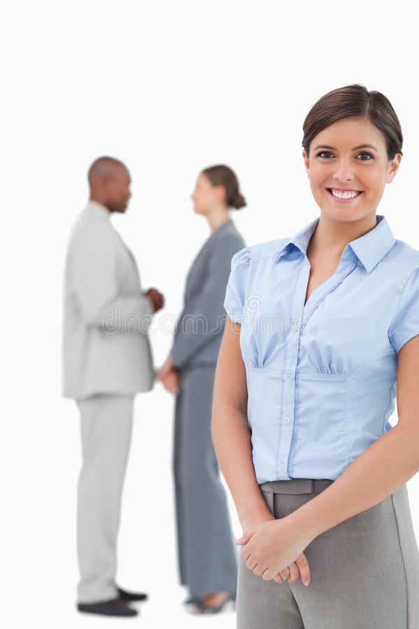 Glimlachende onderneemster met sprekende medewerkers achter haar stock foto's
