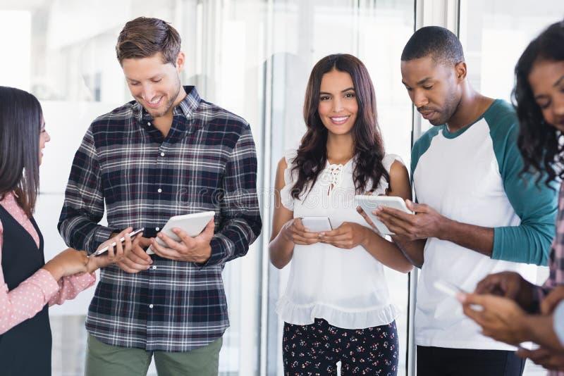 Glimlachende onderneemster met team die mobiele telefoons en digitale tabletten gebruiken royalty-vrije stock foto's