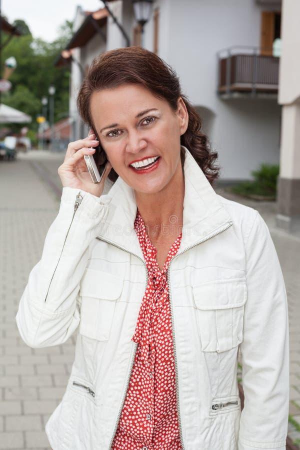 Glimlachende onderneemster op telefoongesprekken met uw celtelefoon stock foto