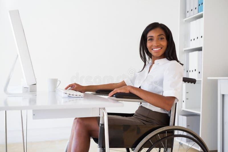 Glimlachende onderneemster in rolstoel die bij haar bureau werken royalty-vrije stock fotografie