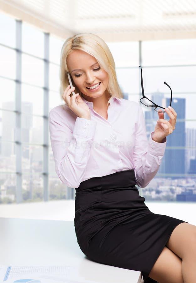 Glimlachende onderneemster of secretaresse met smartphone stock afbeeldingen
