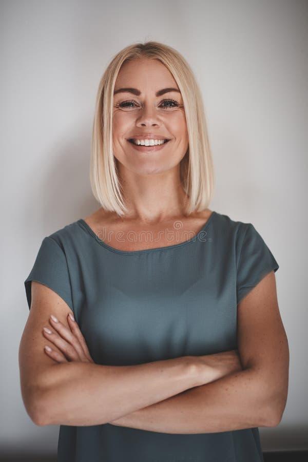 Glimlachende ondernemer met haar die wapens tegen een grijze backgr worden gekruist stock foto's