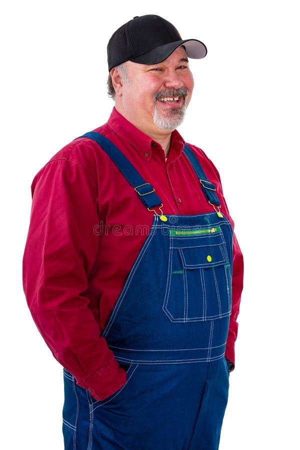 Glimlachende ontspannen arbeider of landbouwer in overall stock foto
