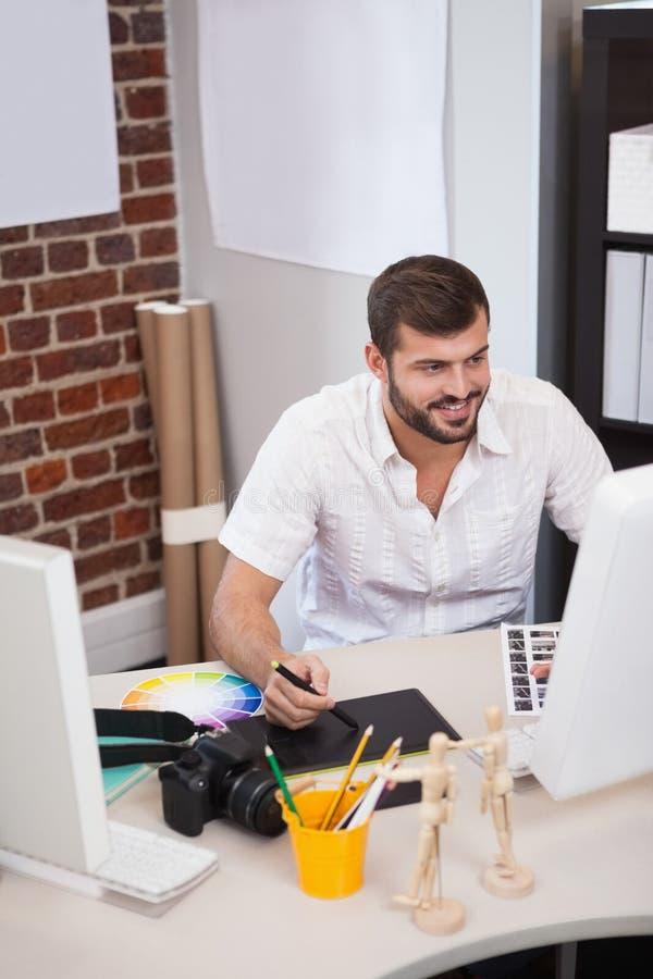 Glimlachende ontwerper die aan zijn computer werken stock afbeelding