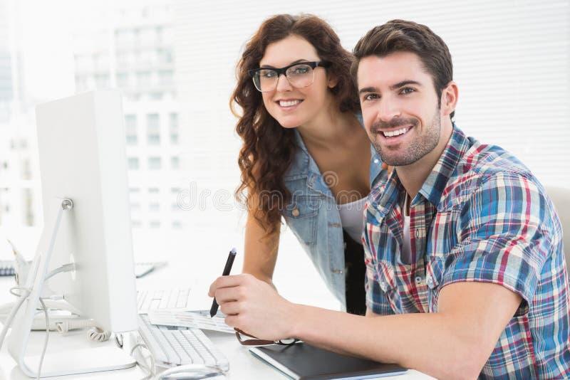 Glimlachende ontwerpercollega's die becijferaar samen met behulp van royalty-vrije stock afbeelding