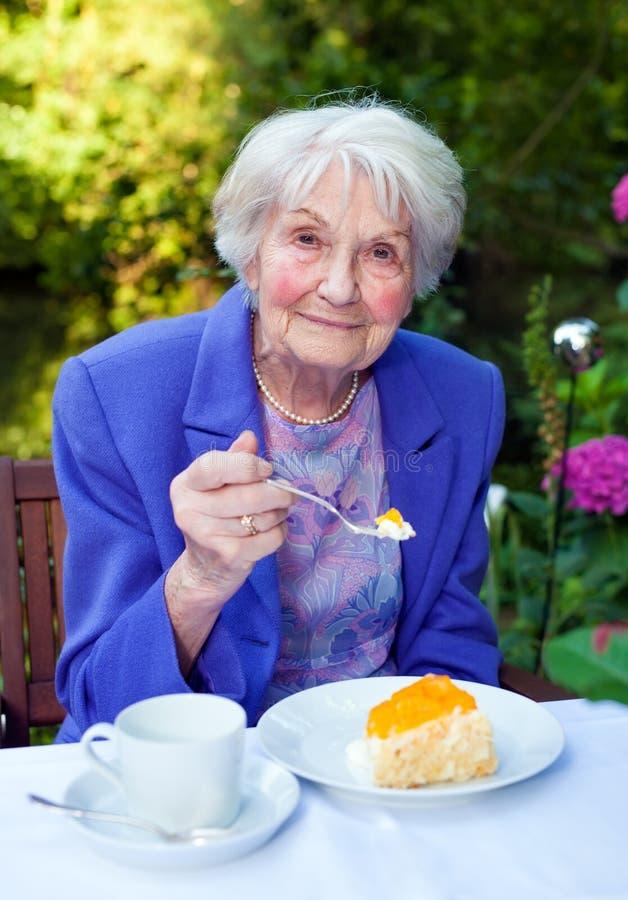 Glimlachende Oude Dame Taking Snacks bij de Tuinlijst royalty-vrije stock afbeelding
