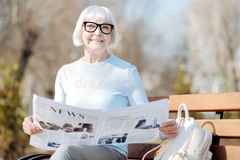 Glimlachende oude vrouw die een krant lezen royalty-vrije stock fotografie