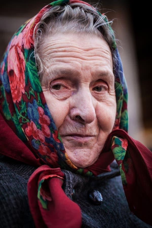 Glimlachende oude vrouw met een sjaal stock afbeeldingen