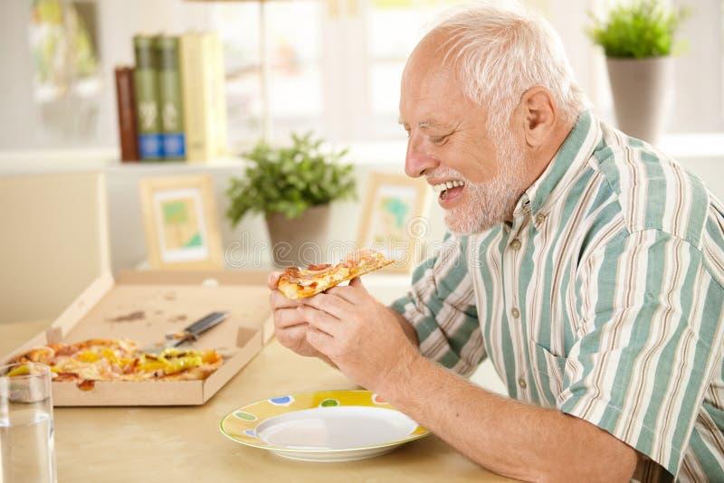 Glimlachende oudere mens die pizzaplak eet royalty-vrije stock afbeelding