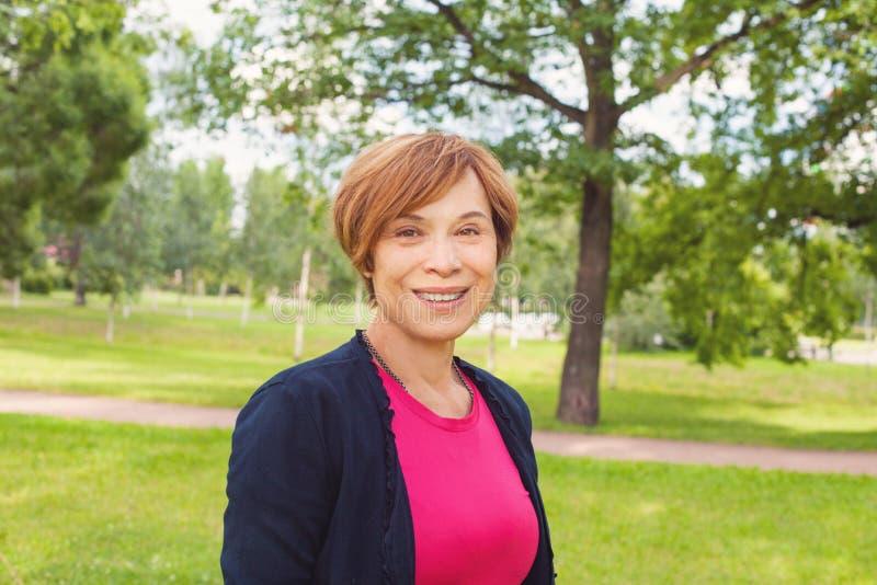 Glimlachende oudere vrouw die in park lopen Bejaarde met rood kort kapsel in openlucht Rijpe Schoonheid royalty-vrije stock foto's