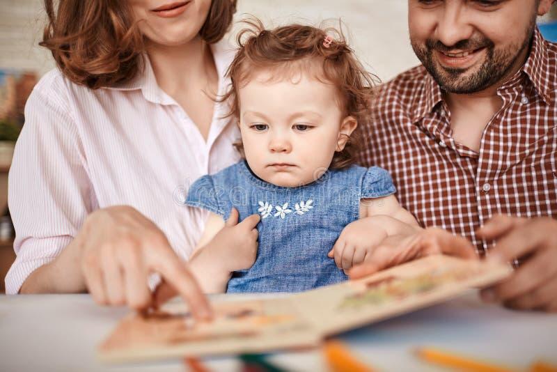 Glimlachende Ouders die Fairytales lezen aan Leuk Meisje royalty-vrije stock afbeelding