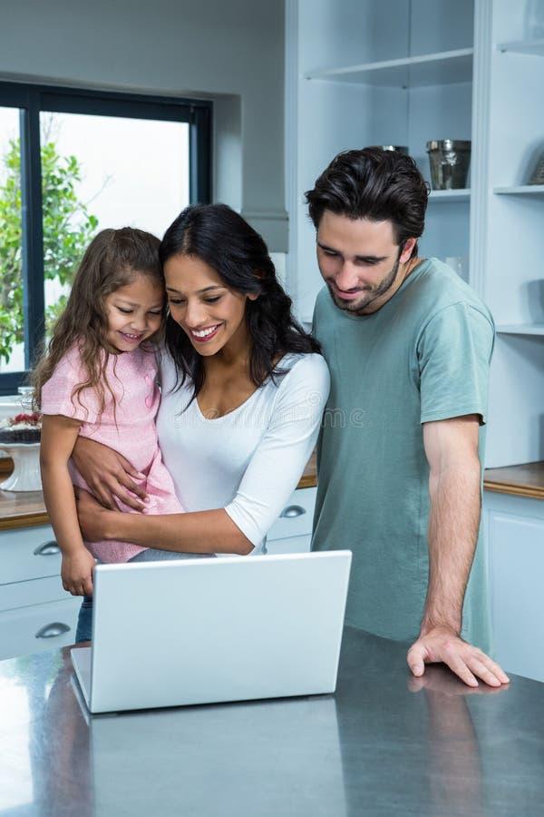 Glimlachende ouders die laptop met dochter met behulp van stock foto