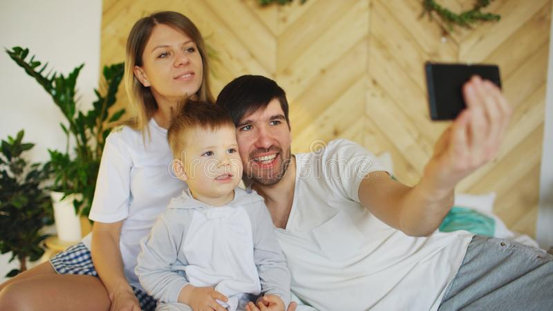 Glimlachende ouders met baby die selfie familiefoto op bed thuis nemen royalty-vrije stock afbeelding