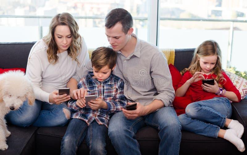 Glimlachende ouders met kinderen die tijd het spelen met smartph besteden stock fotografie