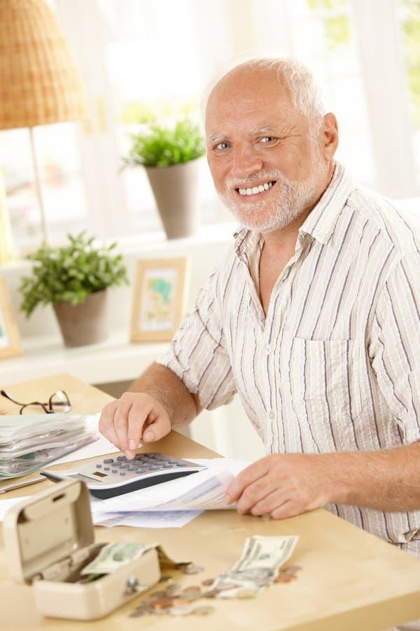 Glimlachende Oudste Bij Financiële Activiteit Stock Afbeeldingen